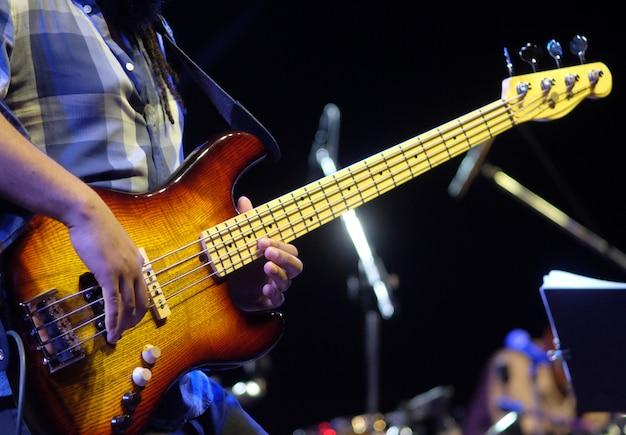 Gitarist die elektrische basgitaar speelt op een jazzconcert