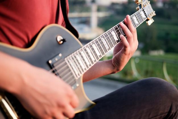 Gitarist die elektrische gitaar in openlucht speelt
