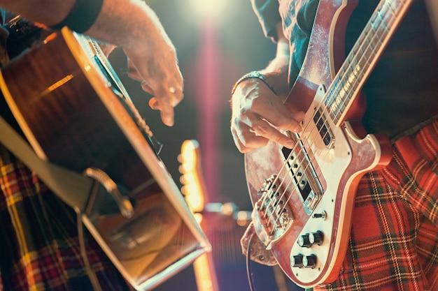 Gitarist en bassist popmuzikanten tijdens een groepsoptreden.