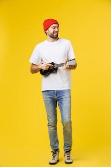 Gitarist man speelt op de elektrische gitaar met heldere emoties, geïsoleerd op geel.