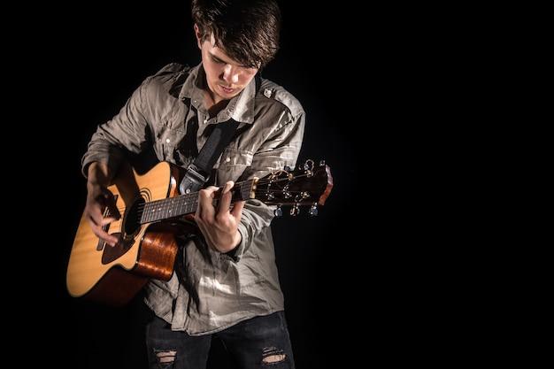 Gitarist, muziek. een jonge man speelt een akoestische gitaar op een geïsoleerde zwarte achtergrond. puntig licht