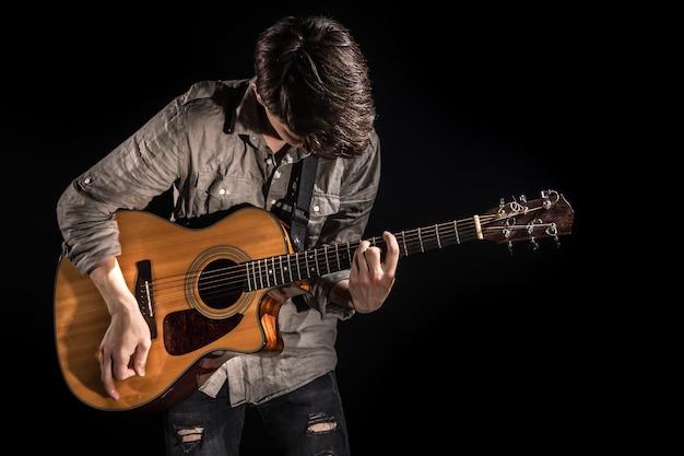 Gitarist, muziek. een jonge man speelt een akoestische gitaar op een geïsoleerde zwarte achtergrond