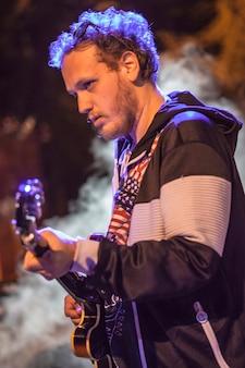Gitarist ondergedompeld in rook en schijnwerpers tijdens een live nachtconcert