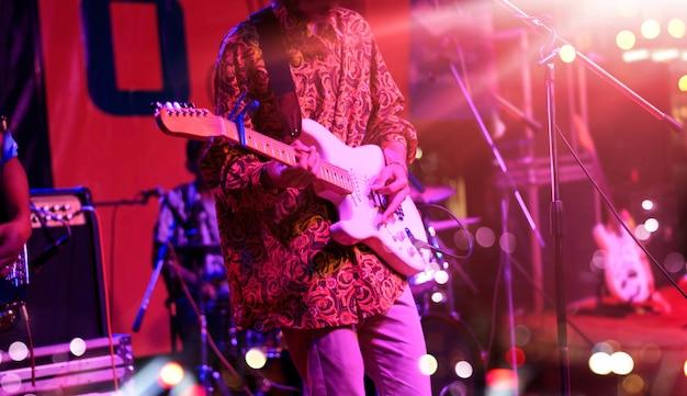 Gitarist op het podium met rode verlichting voor de achtergrond.