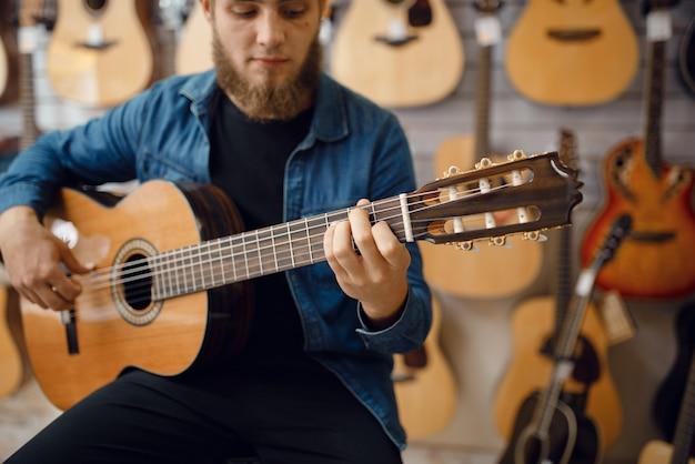 Gitarist speelt op akoestische gitaar in muziekwinkel