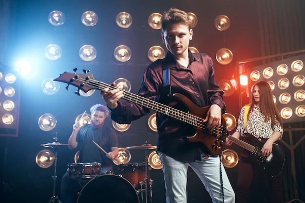 Gitarist speelt op basgitaar, rockband, podium met verlichting
