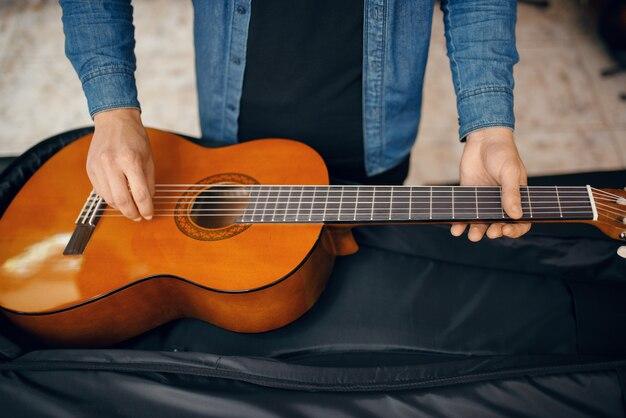 Gitarist stopt gitaar in koffer, muziekwinkel