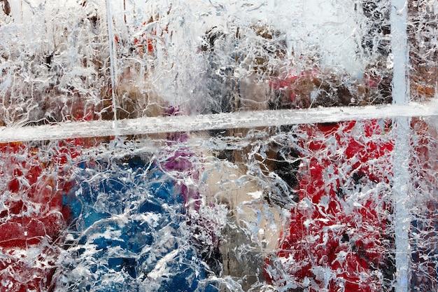 Glaciale transparante muur van ijs met interessante tekeningen en patronen en kleurrijke voorwerpen erachter.