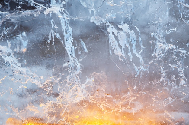 Glaciale transparante muur van ijs met interessante textuur en licht erachter. close-up, achtergrond.