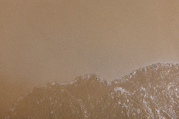 Glad fijn zand en helder water met bubbels.