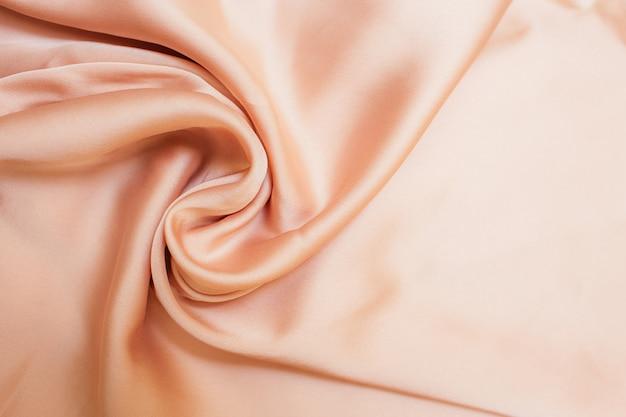 Gladde biege stoffendoektextuur met plooien en wawes. sluit omhoog abstracte achtergrond. biege drapeerde zijde