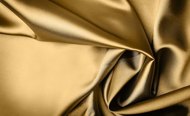 Gladde elegante gouden satijnen achtergrond