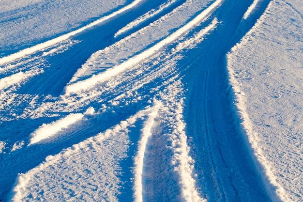 Gladde en gebogen palen van de wielen van auto's in de sneeuw op een besneeuwde weg, een foto van een close-up van een kruispunt onder de sneeuw