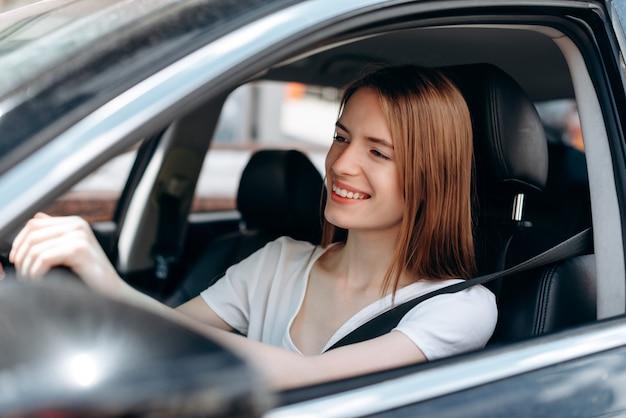 Gladness jonge vrouw besturen van een auto en gelukkig lachend.