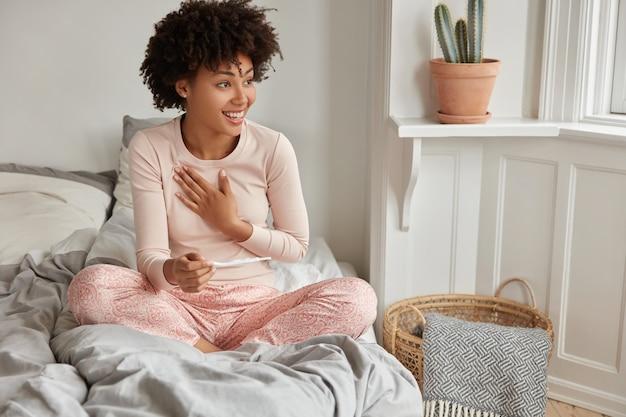 Glaf toekomstige moeder met afro-kapsel, gekleed in een casual pyjama