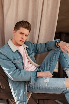 Glamour aantrekkelijke jonge man in modieuze denim jasje in vintage t-shirt in trendy jeans geniet van buiten ontspannen. knappe sexy man in jeans kleding op straat. alledaagse jeugdlook. informele stijl.