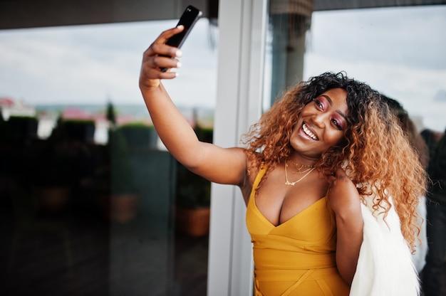 Glamour afro-amerikaanse vrouw in gele jurk en witte wollen cape selfie maken op telefoon.