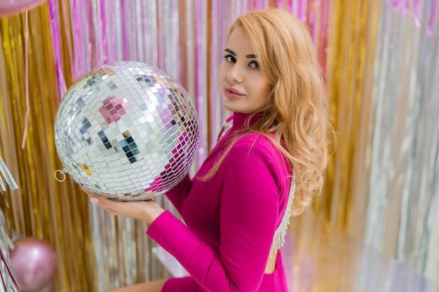 Glamour blonde vrouw in luxe roze jurk poseren met discobal