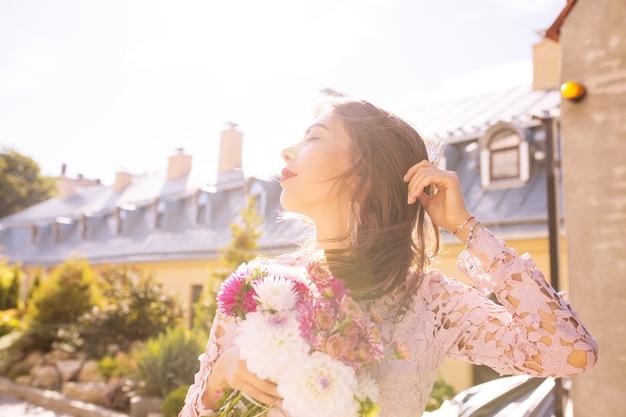 Glamour brunette model met een boeket bloemen in zonnestralen