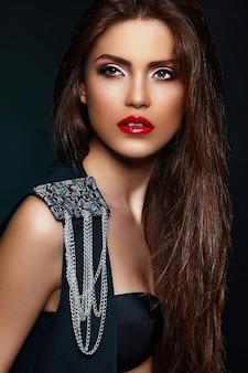 Glamour close-up portret van mooie sexy stijlvolle brunette blanke jonge vrouw model met lichte make-up, met rode lippen, met perfecte schone huid met juwelen in zwarte doek