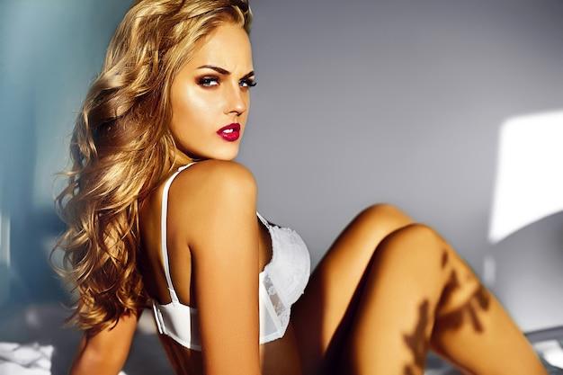 Glamour close-up portret van mooie sexy stijlvolle jonge vrouw model liggend op wit bed met lichte make-up, met rode lippen, met perfecte schone huid in witte lingerie