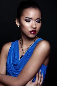 Glamour close-up portret van mooie sexy zwarte jonge stijlvolle vrouw model in blauwe jurk met accessoires met lichte make-up met een perfecte schone huid
