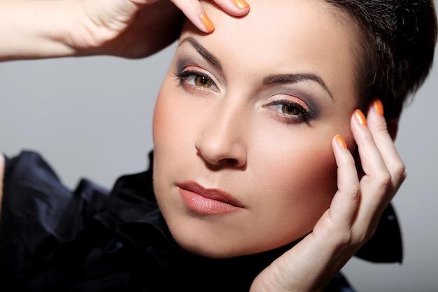 Glamour en prachtige brunette aan haar gezicht te raken