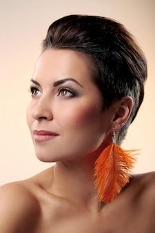 Glamour en prachtige brunette met veren oorbel