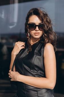 Glamour en sexy vrouw in zwarte latexkleding en zonnebril.