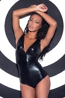Glamour fotomodel. mooie jonge afro-amerikaanse vrouw met make-up en kapsel poseren tegen gestripte achtergrond