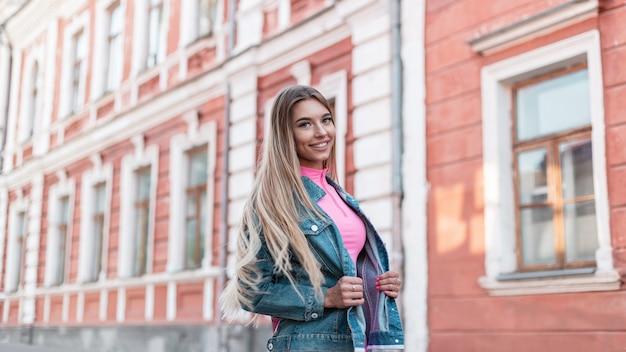 Glamour gelukkige jonge vrouw blond met lang haar in vintage roze korte broek in een stijlvolle roze top in een trendy denim jasje lopen op straat op een zomerdag. leuke blije meisjesmannequin met glimlach