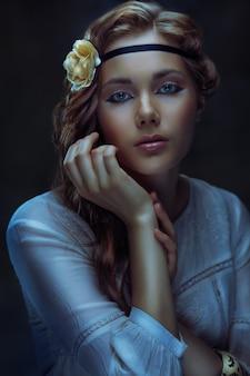 Glamour hippie meisje poseren op donkere achtergrond, afgezwakt low key portret
