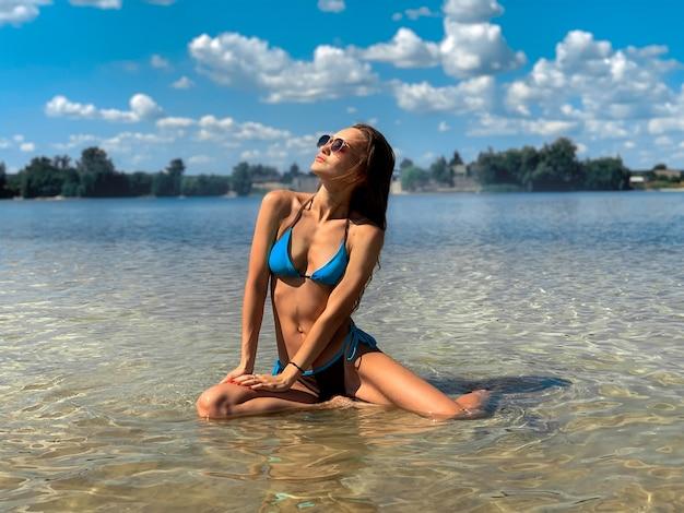 Glamour jonge brunette vrouw in blauwe zwembroek poseren op het strand in warme zomerdag