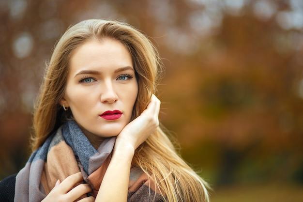 Glamour langharige blond meisje draagt jas, poseren in de botanische tuin. ruimte voor tekst