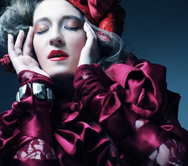 Glamour mannequin in elegant rood kostuum met rode hoed