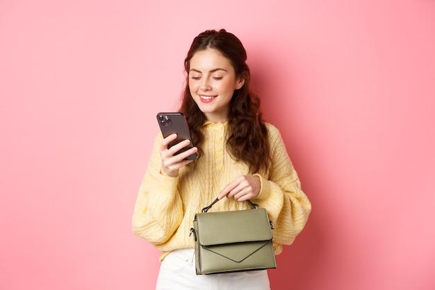 Glamour meisje met portemonnee en sms-bericht op smartphone, gsm-scherm lezen met zorgeloze glimlach, staande over roze muur