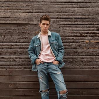 Glamour modieuze jonge man in roze stijlvol t-shirt met denim blauwe jas in spijkerbroek staat in de buurt van houten vintage gebouw op straat. knappe trendy man mannequin met kapsel in de stad.