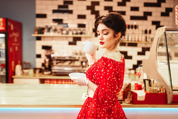 Glamour pin-up girl met make-up drinkt koffie in retro café, 50 amerikaanse mode. rode jurk met stippen, vintage stijl