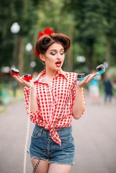 Glamour pin-up girl met retro roterende telefoons