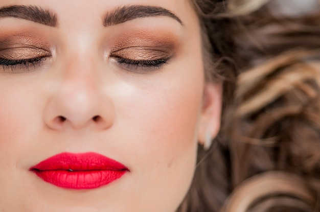 Glamour portret van mooi vrouwelijk model met verse dagelijkse make-up en romantisch golvend kapsel. fashion glanzende highlighter op de huid, sexy gloss lippen make-up en donkere wenkbrauwen