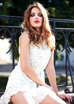 Glamour schoonheid portret van mooie sensuele blanke jonge vrouw model met avond make-up in witte zomerjurk poseren op straat