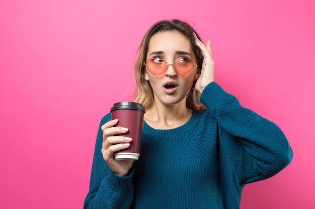 Glamour vrouw in bril in een blauwe trui met een drankje van koffie op een roze achtergrond