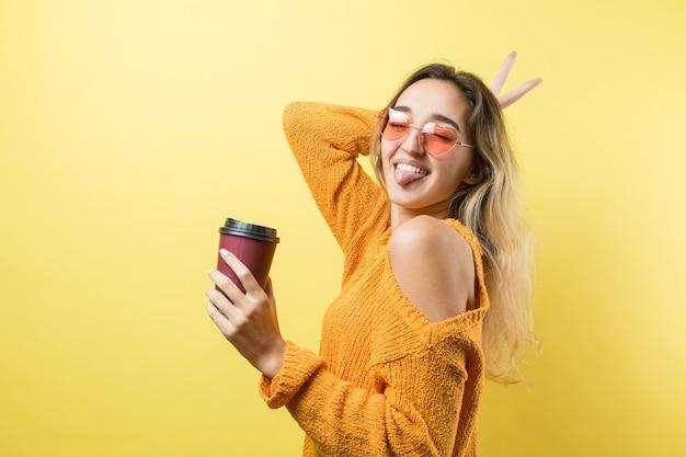 Glamour vrouw in glazen in een oranje trui met een drankje van koffie op een gele achtergrond