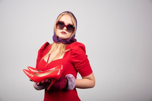 Glamour vrouw in rode outfit poseren met paar hakken.