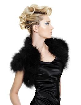 Glamour vrouw in zwarte bont jurk met modern kapsel poseren op witte muur