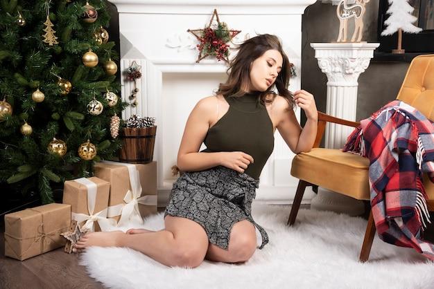 Glamour vrouw in zwarte top zittend op wit tapijt bij de open haard