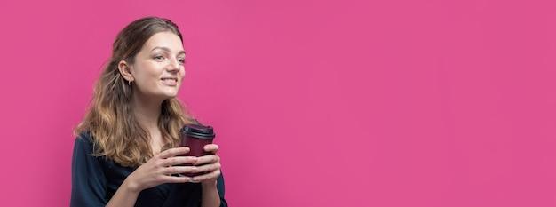 Glamour vrouw met een drankje van koffie op een roze achtergrond.