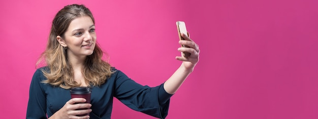 Glamour vrouw met een drankje van koffie op een roze achtergrond