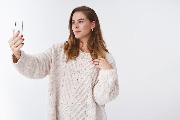 Glamour zelfverzekerde aantrekkelijke vrouw kort haar losse trendy trui poseren verlengde arm smartphone op zoek mobiel display nemen selfie vastleggen brutale foto post internet, witte achtergrond