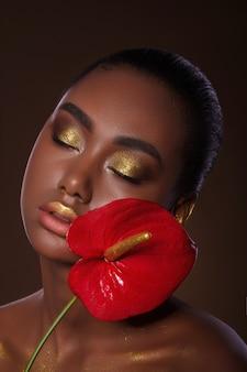Glamoureus afrikaans meisjesportret met rode exotische bloem. gouden make-up. mooi gezicht.